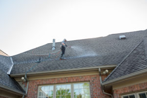 A harnessed man cleans the roof of a home with a Soft Wash roof cleaning system to remove algae and other bacterial contaminants.