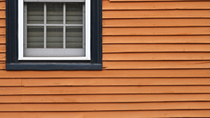 Photo of orange siding on a building with a window on the left side.